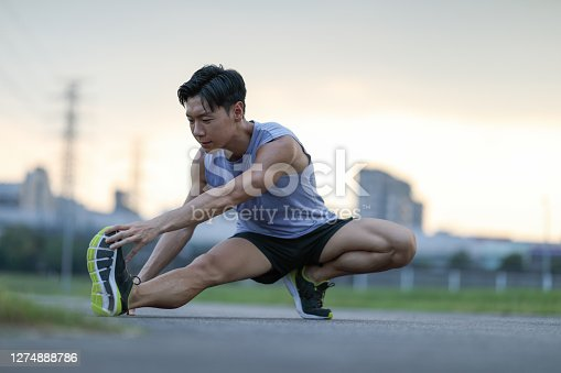 young man stretching and warming up before running in the city park at dusk