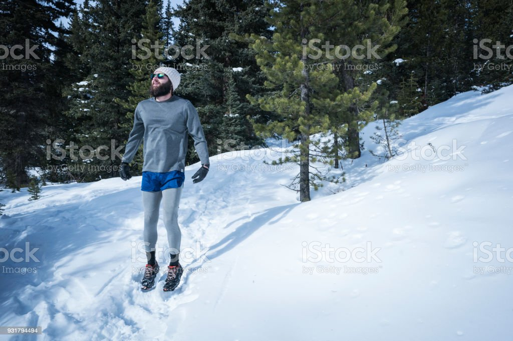 Man warming up before trail running in winter stock photo