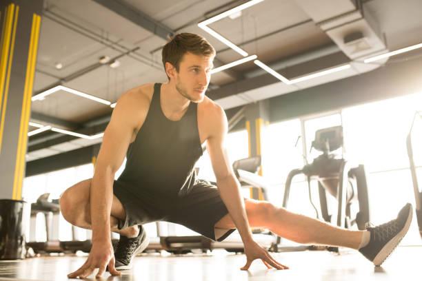 Mann wärmt sich im Fitnessstudio auf – Foto
