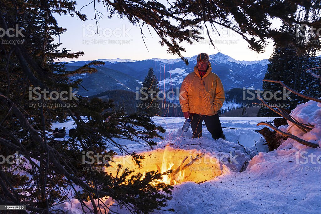 Man Warming Up in Winter by Fire stock photo
