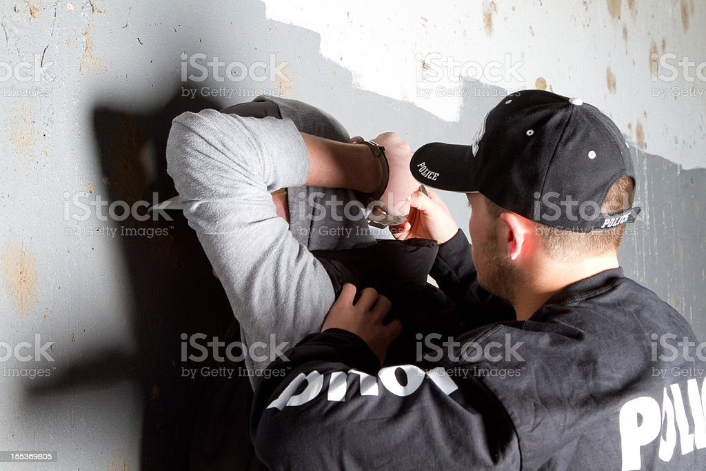Man was arrested by police who put him up against the wall royalty-free stock photo