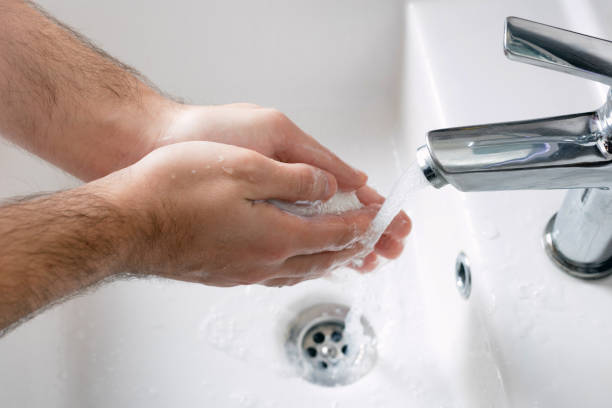 Man wash his hands deeply under a faucet with running water. Hand washing is very important to avoid the risk of contagion from coronavirus and bacteria stock photo