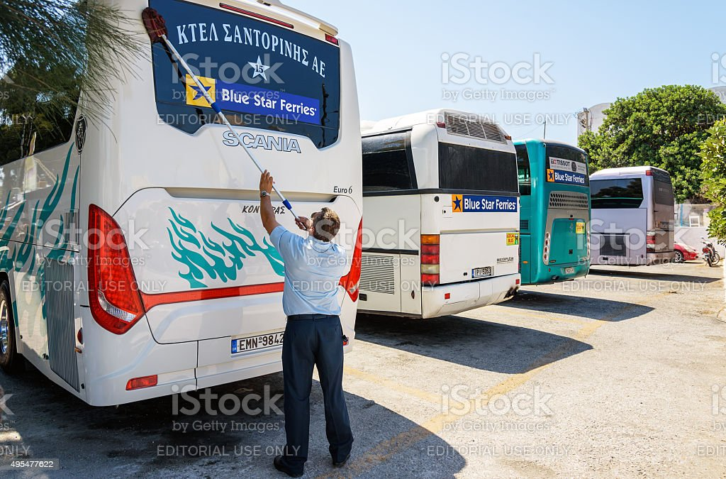 Man washes bus windows at bus station stock photo