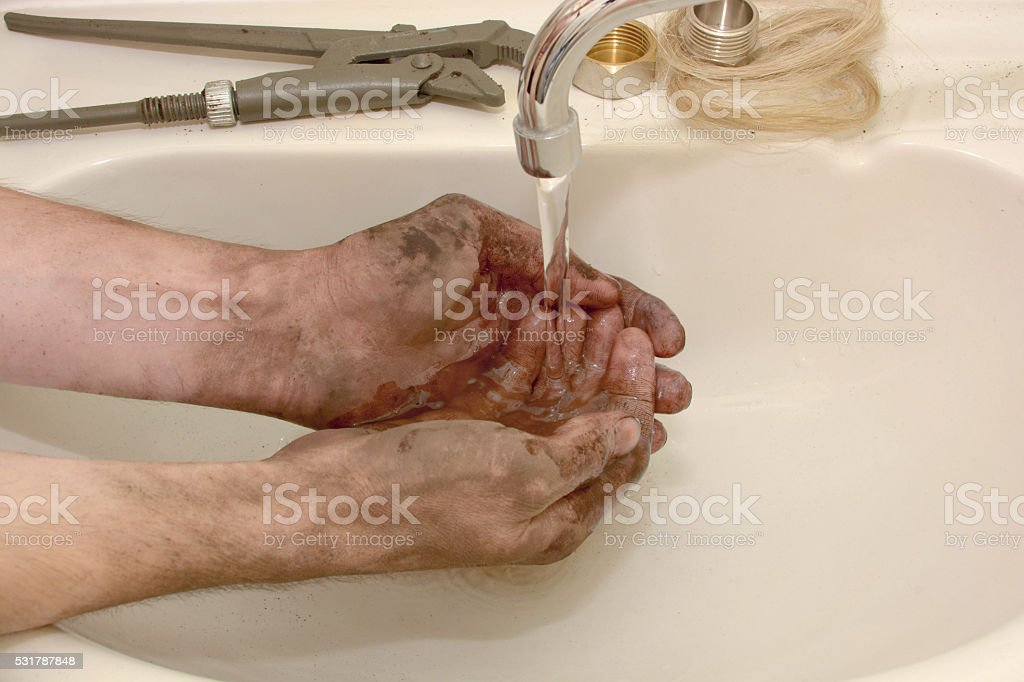 man washes hands dirty stock photo