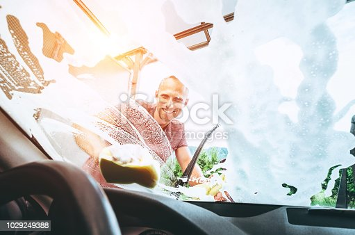 Man washes his car front window