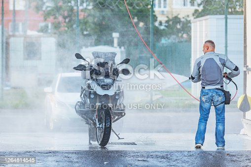 Korolev, Russia - August 07, 2020: Man washes his motorbike on the open air.