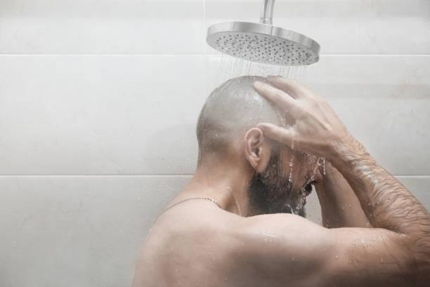 ein mann wäscht in der dusche. seitenansicht. - dusche stock-fotos und bilder