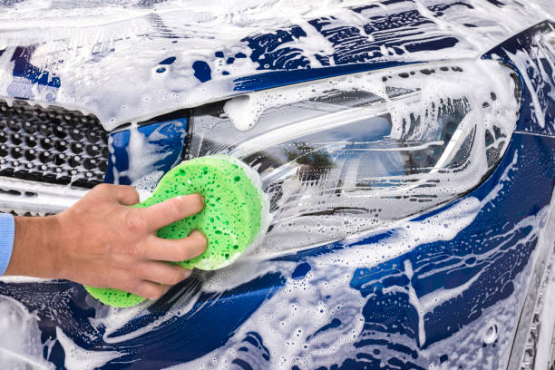 mann wäscht ein seifenblaues auto mit einem grünen schwamm. - auto trennwand stock-fotos und bilder