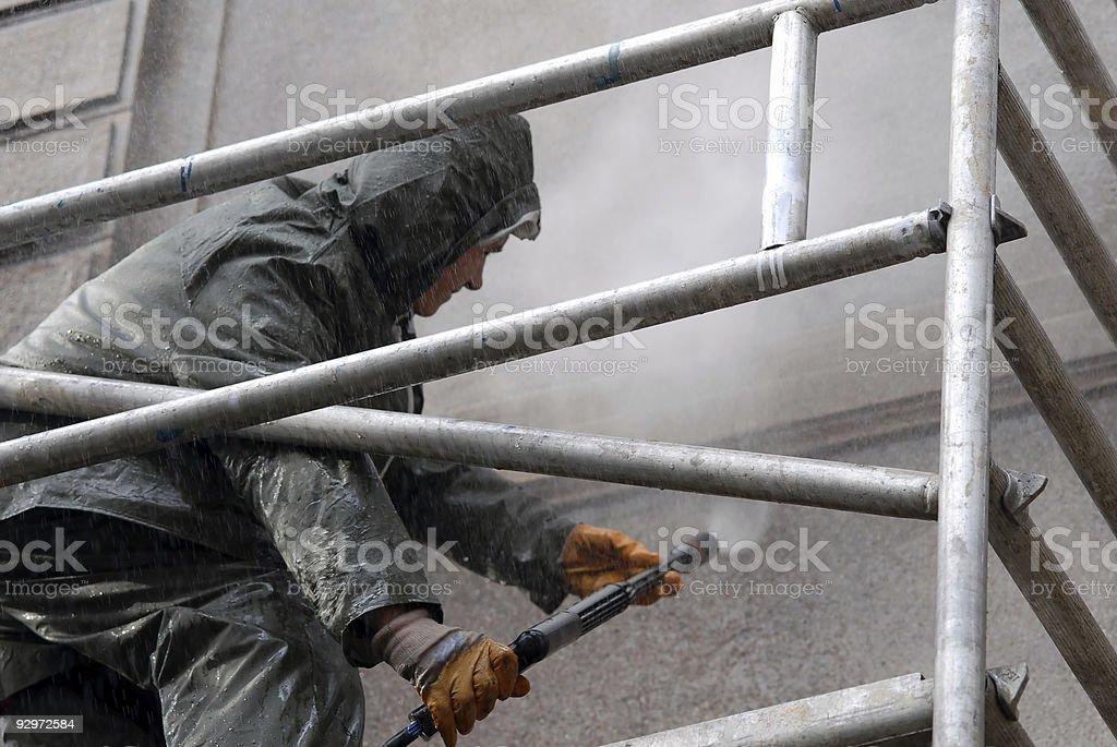 Man washing building facade royalty-free stock photo