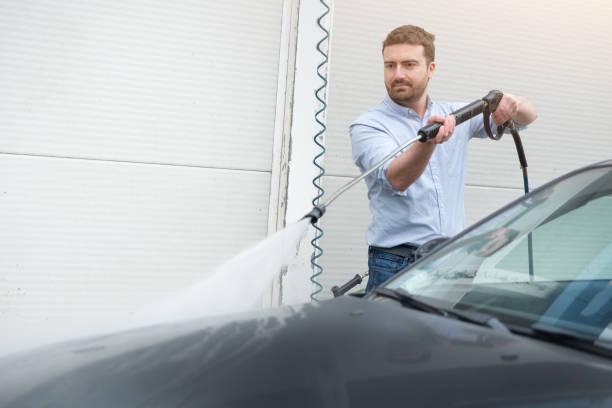 man washing car in car wash station - dampfreiniger fenster stock-fotos und bilder