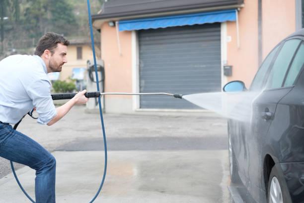 mann waschen auto in auto-waschanlagen-station - dampfreiniger fenster stock-fotos und bilder