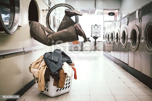 A man in 1980's style does his laundry at an old school laundromat.  He climbs into the dryer to reach some clothes in the very back, appearing to fall inside.  Horizontal image with copy space.