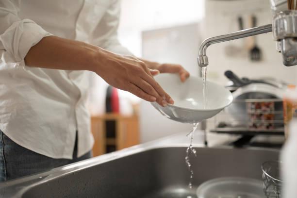 man washing dish in kitchen stock photo