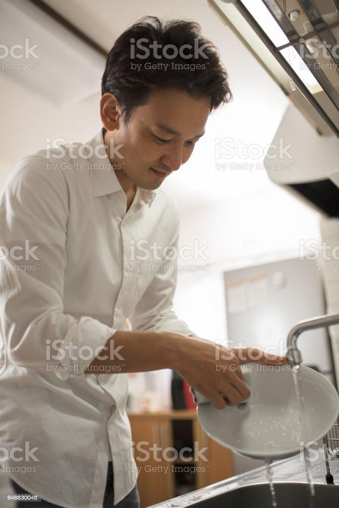 prato de lavar roupa de homem na cozinha - foto de acervo