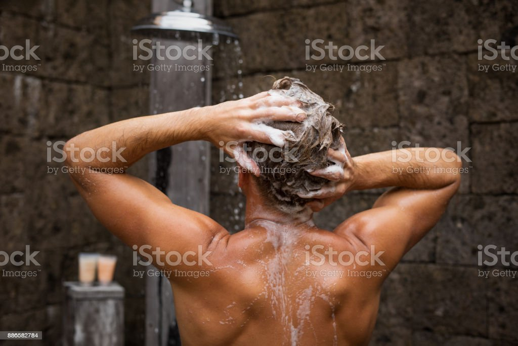 Man washing hair in shower stock photo