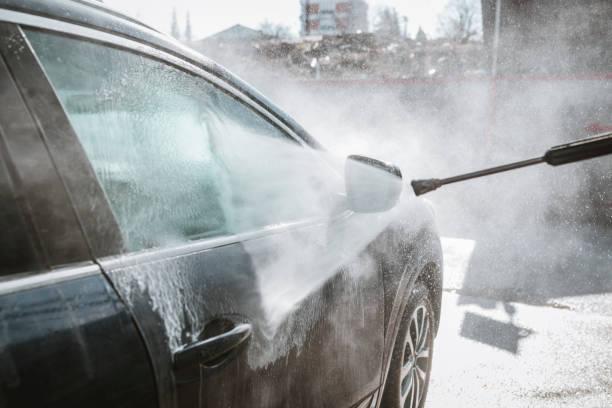 Homme lavant sa voiture avec le lavage à haute pression - Photo