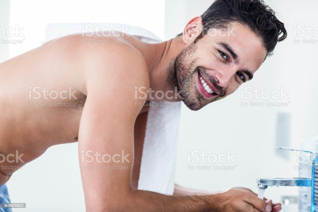 Man washing his face in sink stock photo