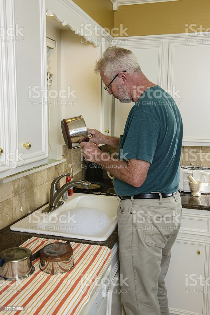 A senior man standing at the kitchen sink washing cooking pots.