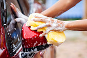 istock Man washing red car with sponge and soap 980515328