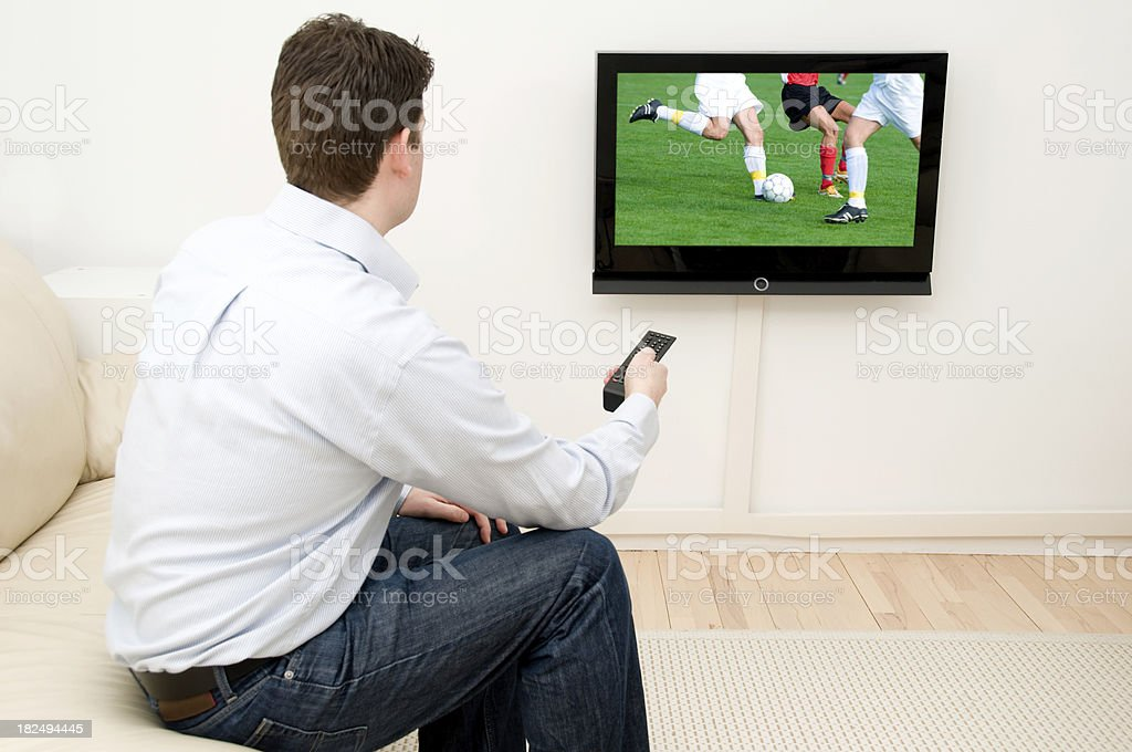 Man watches football match on tv  as players compete stock photo