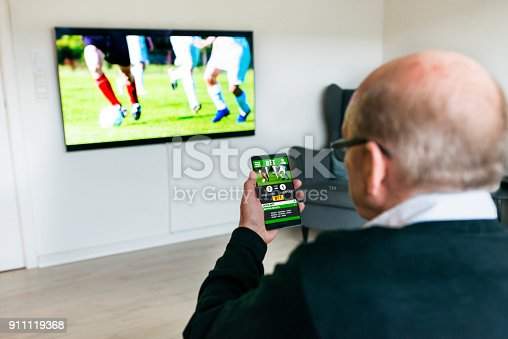 istock Man watches soccer match on television and bets on the game with betting app on phone 911119368