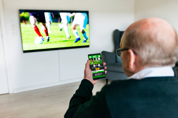 man watches soccer match on television and bets on the game with betting app on phone - smartphone addiction not groups stock pictures, royalty-free photos & images
