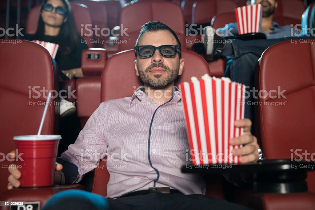 Man watching a 3d movie with some popcorn stock photo
