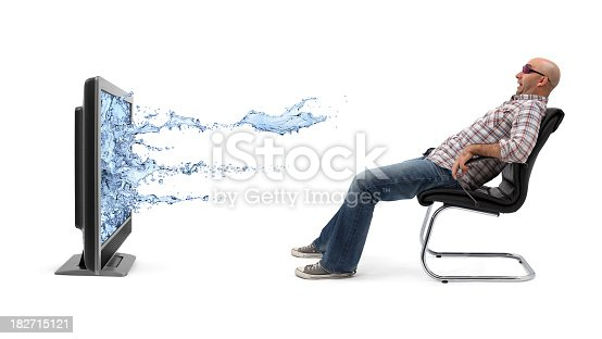 A man sitting on armchair and watching 3D (three-dimensional) television with 3D glasses. Water flowing out of a flat screen TV and he is amazed and scared. Isolated on white background.