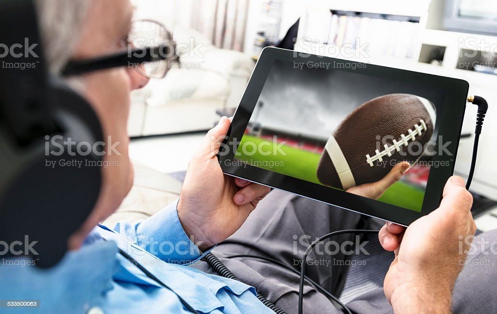 Man watching a football game on the tablet stock photo