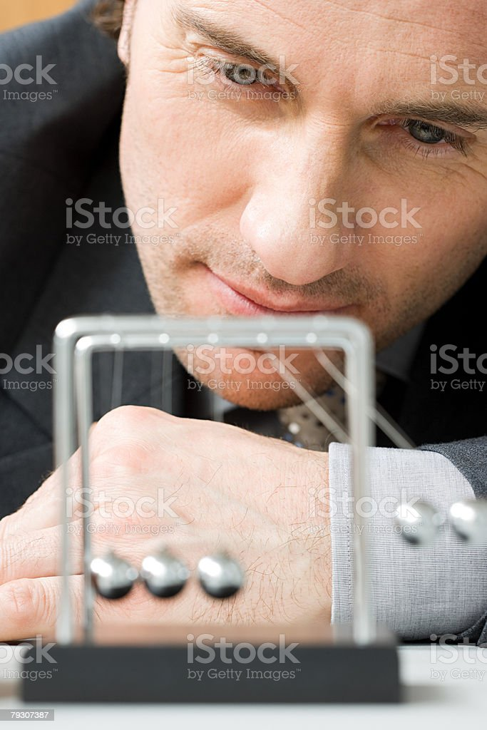 Ein Mann vor einer newtons Wiege in motion Lizenzfreies stock-foto
