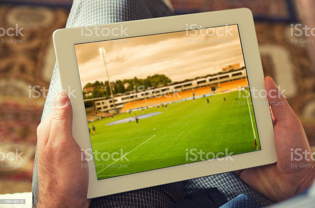 Man watching a soccer tv game on digital tablet stock photo