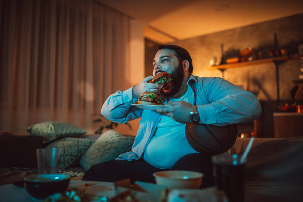 Man watching a sports match and eating burger One man, sitting at home, eating burgers and watching a sports match alone. man cave couch stock pictures, royalty-free photos & images