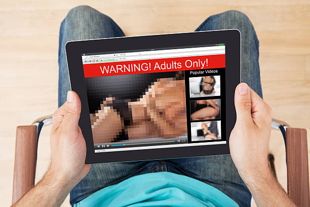 man watching adult movie on digital tablet - filme sehen stock-fotos und bilder