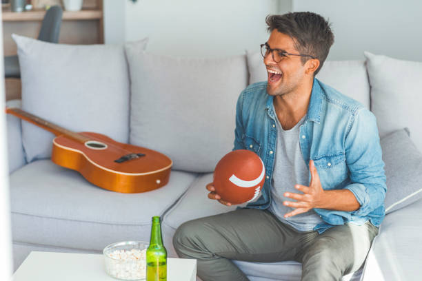 Man watching American football at home sitting in couch. Young man watching american football game on television celebrating. Crazy happy jumping on sofa couch at home with ball beer bottle and popcorn looking excited and cheerful man cave couch stock pictures, royalty-free photos & images