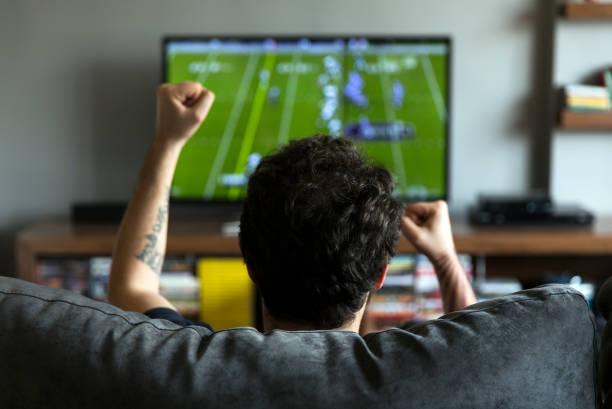 Man watching American football Man watching American football on tv and cheering american football sport stock pictures, royalty-free photos & images
