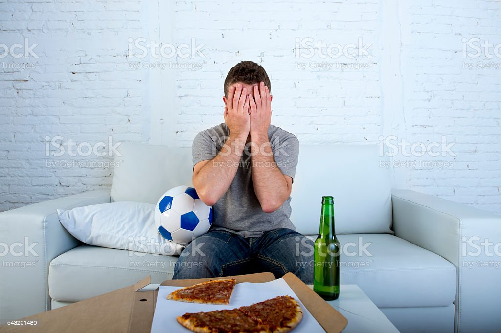 man watching football game on tv covering eyes sad disappointed stock photo