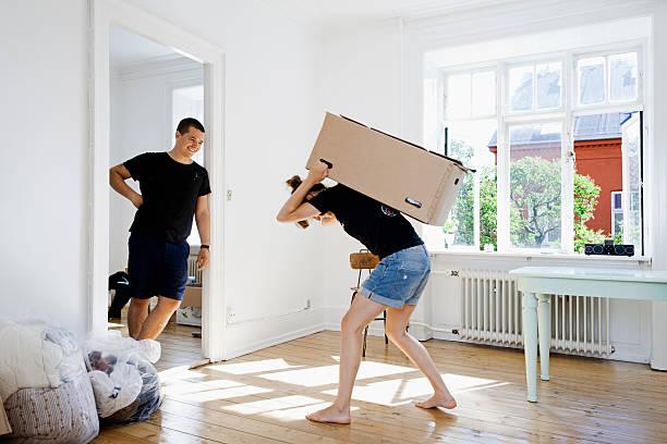 man watching girlfriend carry heavy box - 重的 個照片及圖片檔