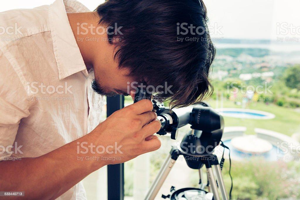 man watching girls  at the pool through his telescope stock photo