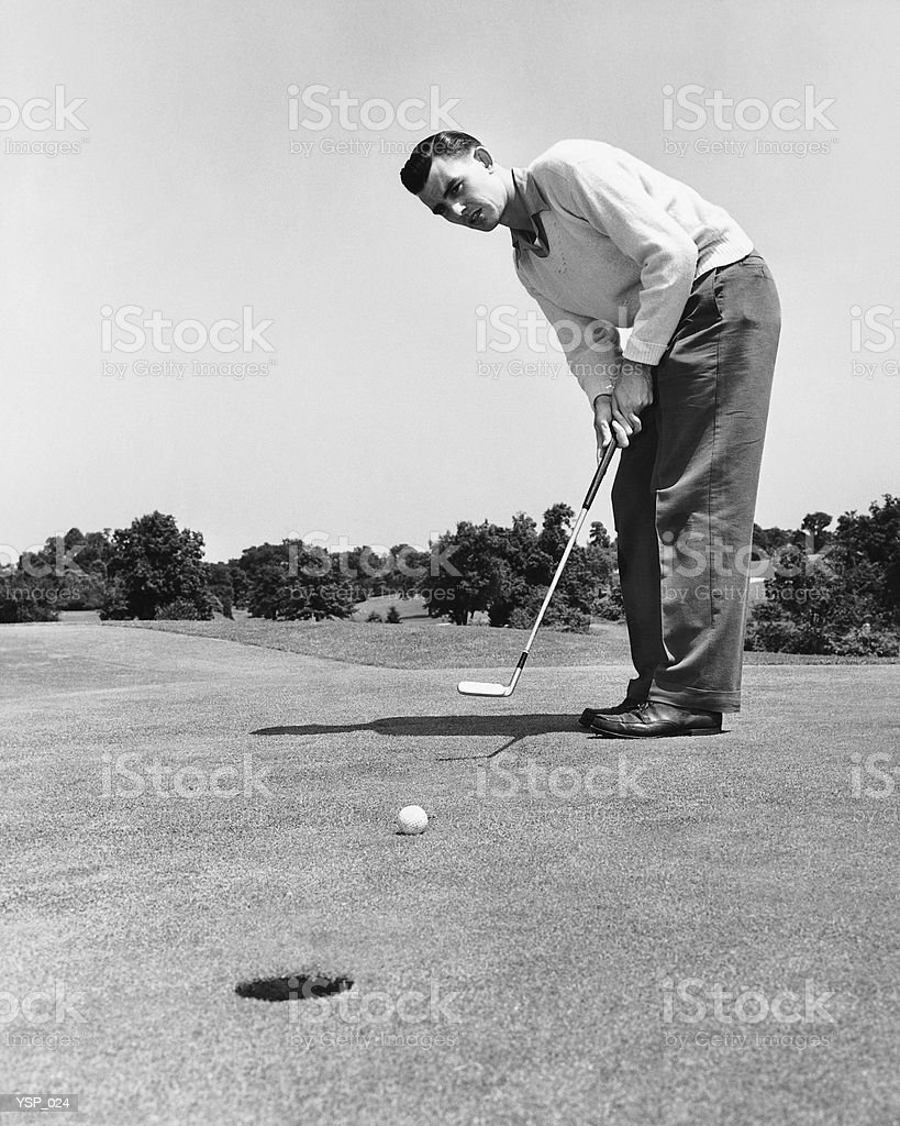 Man watching golf ball after hitting it with putter royalty free stockfoto