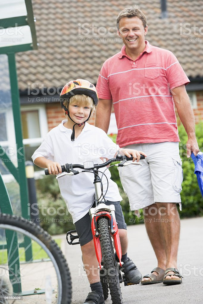 Man watching his son on a bicycle royalty-free stock photo