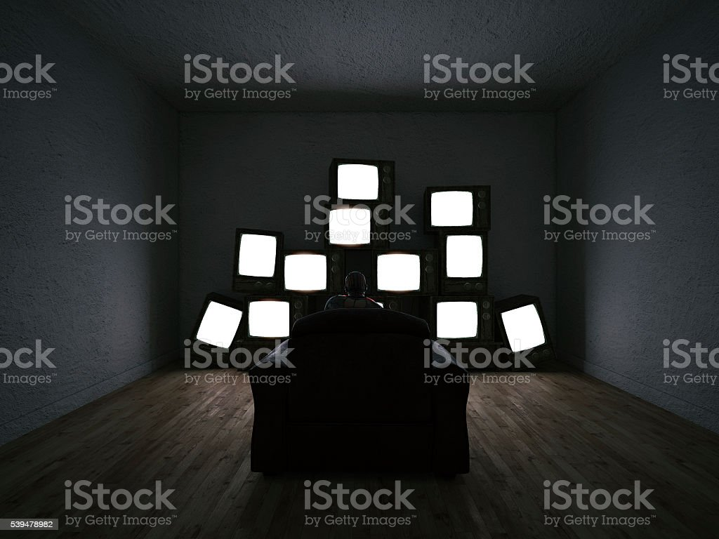 Man watching multiple TV sets stock photo