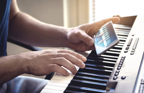 Man watching piano tutorial video with mobile phone. Person practising playing with an online lesson and course. Internet class to learn a new instrument. stock photo
