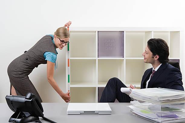 Man watching secretary measure shelf stock photo