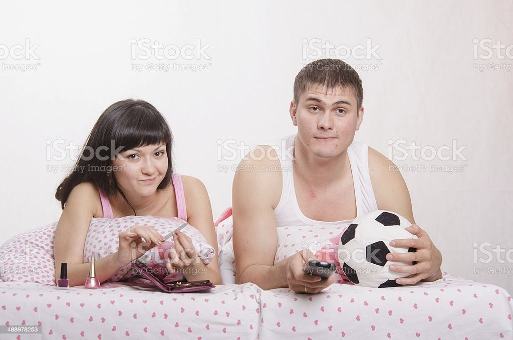 Man watching soccer on TV, manicure girl engaged in bed royalty-free stock photo
