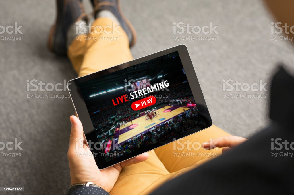 Man watching sports on live streaming online service stock photo
