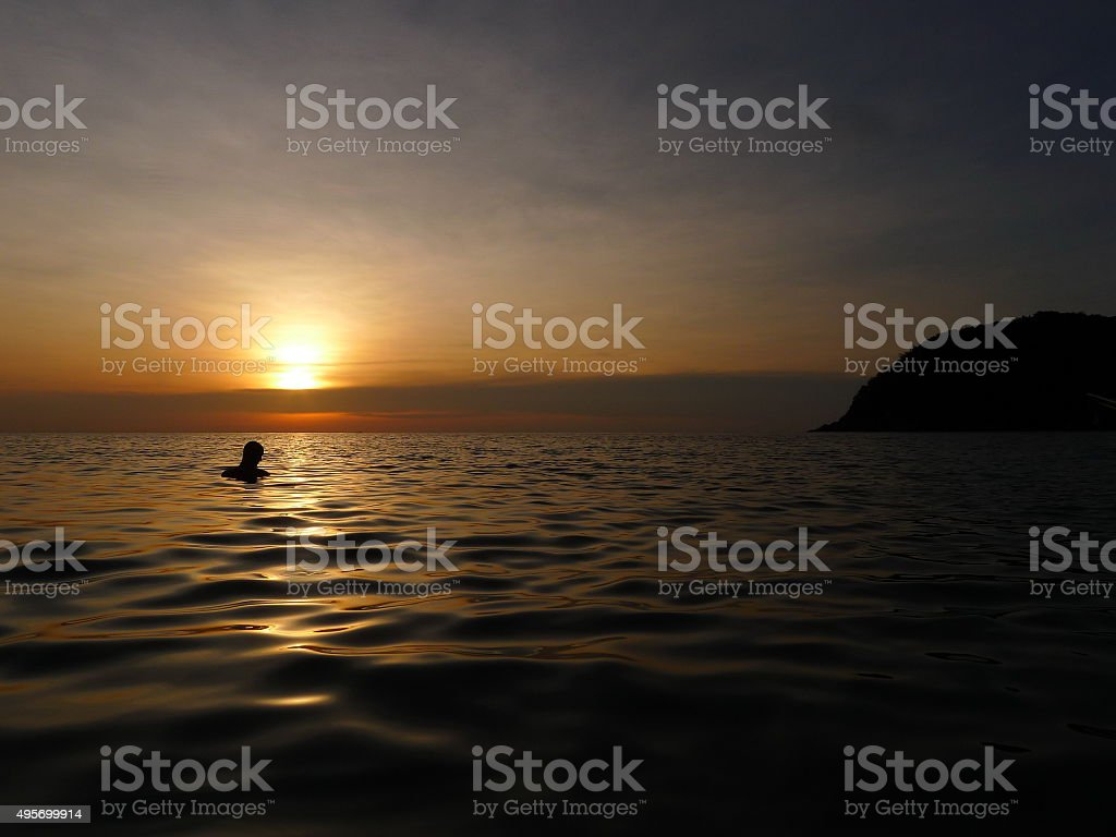 Man watching sunset in the sea stock photo