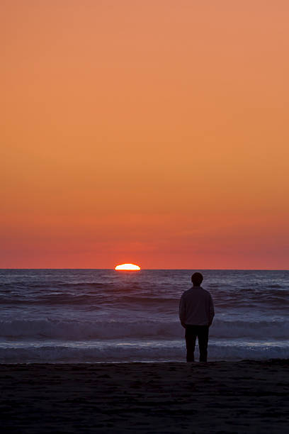 Man watching sunset over the ocean stock photo