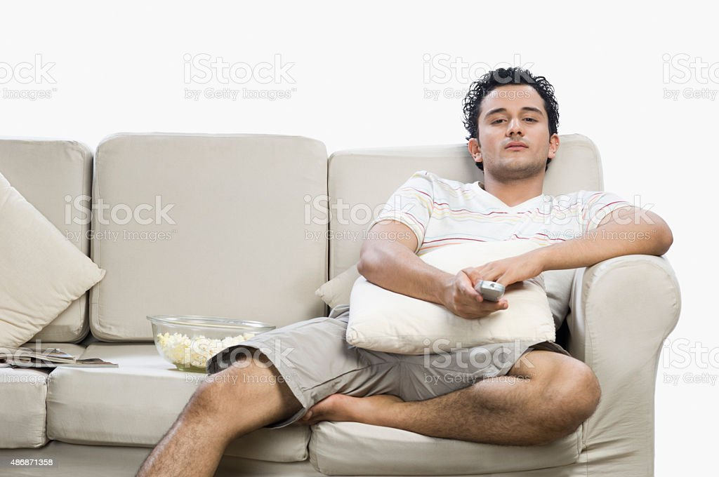 Man watching television and looking surprised stock photo