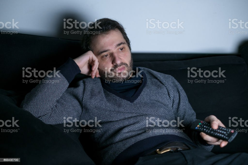 Man watching television at night stock photo