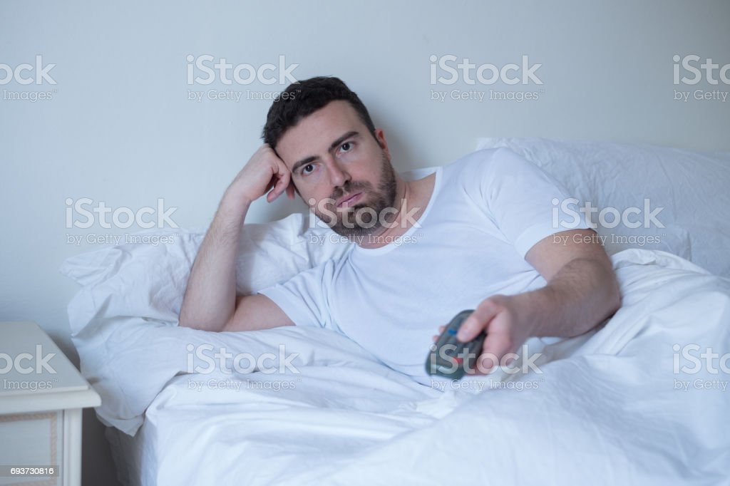 Man watching television lying in bed stock photo